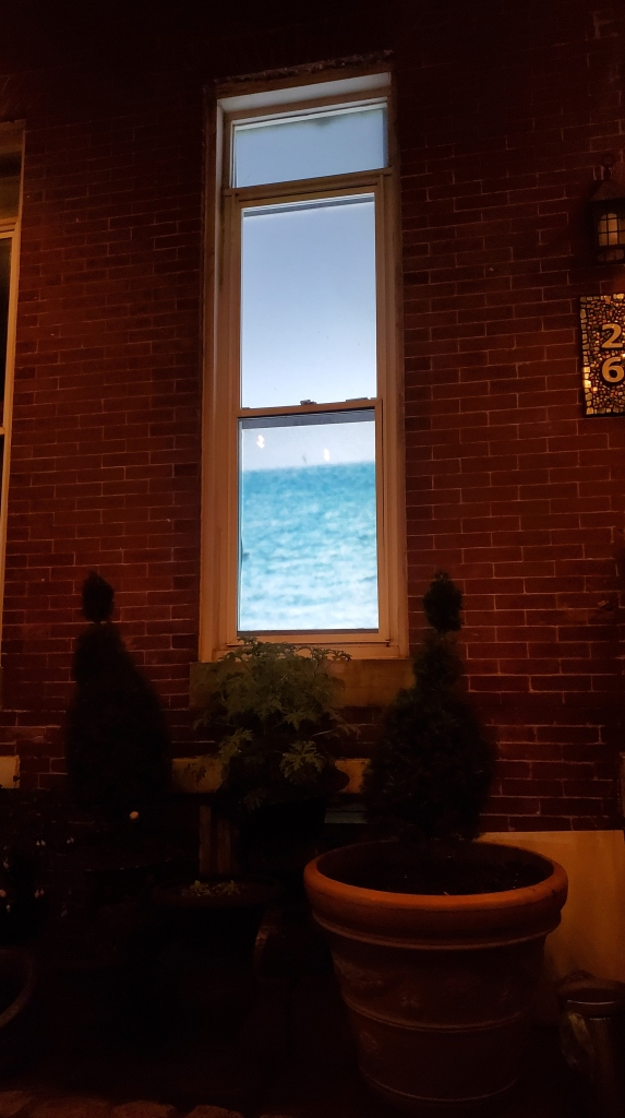 Beach is projected onto a screen inside of a row house window